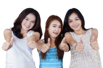 Cheerful teenage girls showing thumbs up