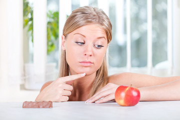 Woman looking at apple and candy, fruit or candy dilemma