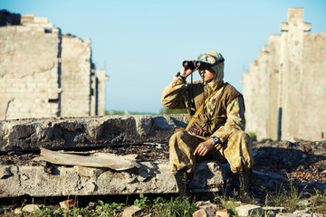 Man in camouflage uniform is looking through the binoculars. Urb