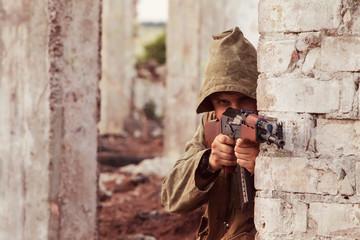 Insurgent in hood with the Kalashnikov machine gun is aiming. Ru