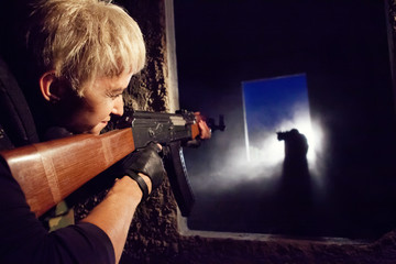 Blond woman with Kalashnikov machine gun is aiming on silhouette