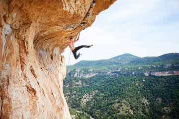 Young man climbing up ledge of cliff
