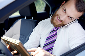 Smiling cool young business man at work in car with technology