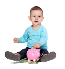 baby boy putting money into the piggy bank