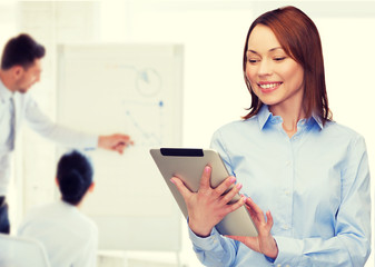 smiling woman looking at tablet pc at office