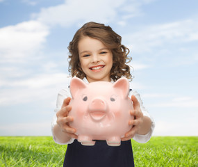 happy girl holding piggy bank