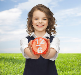 happy girl with alarm clock over summer background