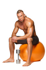Shaped and healthy body man sitting on fitness ball