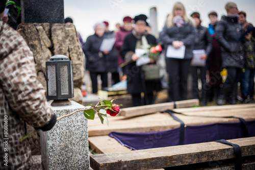 Leinwanddruck Bild Group of mourners staying by the opened grave at a cemetery