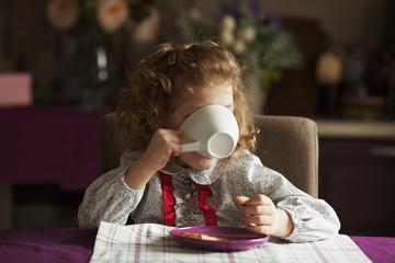 Little girl drinking from a big white cup