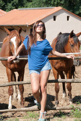 Young girl in the farm surrounded by horses