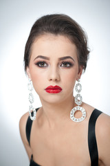 Hairstyle and make up - beautiful female with earrings, studio