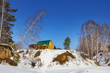 Строящийся дачный дом на берегу реки зимой