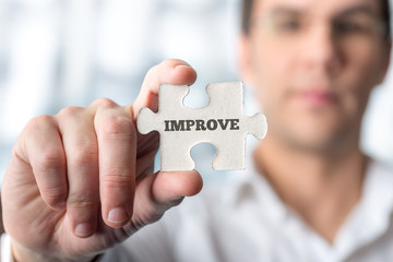 Man holding puzzle piece with word Improve