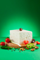 White feta cheese on wooden board and  green background