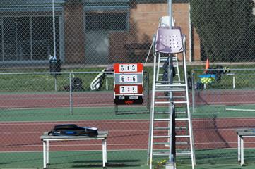 tableau de marque avec chaise sur court de tennis