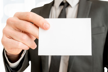 Closeup of businessman showing blank white business card