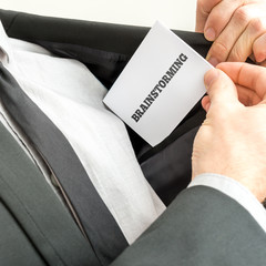 Businessman displaying a card reading Brainstorming