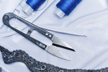 Scissors and blue thread on fabric background.