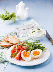 Breakfast with soft-boiled egg, arugula and tomatoes
