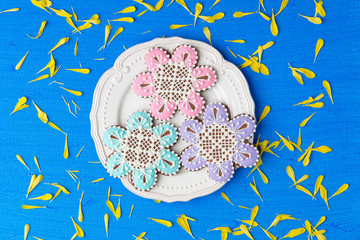 Flowers shaped cookies decorated with ornaments on blue backgrou