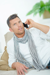Man taking a phone call whilst on the sofa