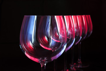 Wine glasses lit by red, blue, lilac nightclub party lights
