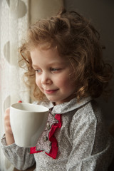 Beautiful little girl with a cup of tea