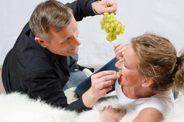 Mann füttert Frau mit Weintrauben