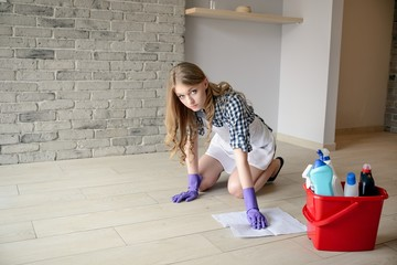 Nervous and tired beautiful young woman washes the floor