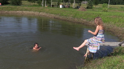 Happy family daughter girl splash pond water and pregnant mother