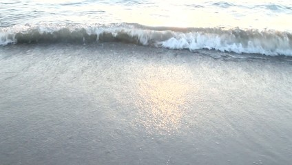 Sea waves washing over the sand on the beach in light of sunset