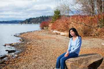 Young teen girl in blue shirt and jeans sitting along rocky lake