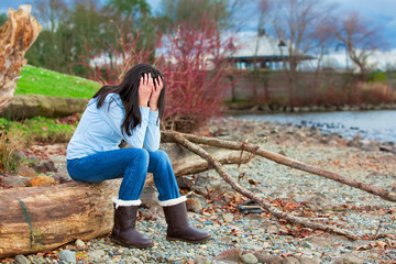 Sad young teen girl sitting on log along rocky beach by lake