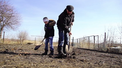 child and grandfather digging shovel earth on a farm, nature