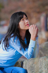 Young teen girl sitting outdoors on rocks praying