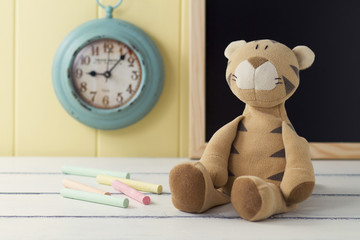 A stuffed animal, chalks, a turquoise clock and a blackboard