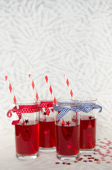 Four festive glasses with red juice and straws