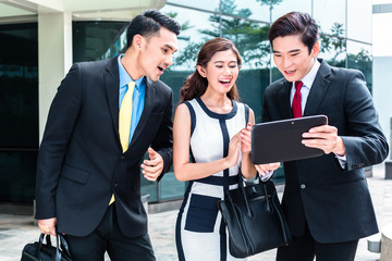 Asian businesspeople working outside on tablet PC