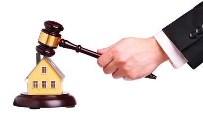 Concept of house sale with gavel in hand, isolated