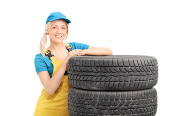 Female mechanic leaning on a stack of used tires
