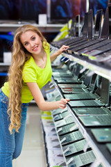 Beautiful young girl at the store chooses laptop