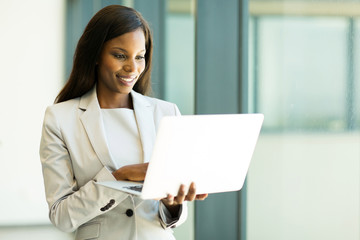 african businesswoman reading email on her laptop