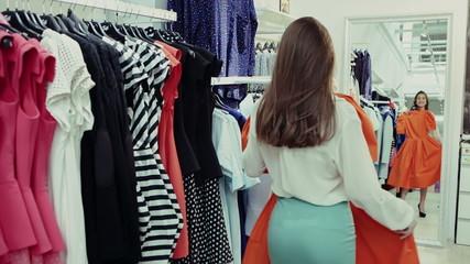 Beautiful girl trying dress near mirror in room