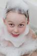 Cute child in soap foam