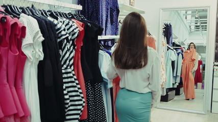 Beautiful girl trying orange dress near mirror in room