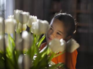 Niña mirando tulipanes blancos