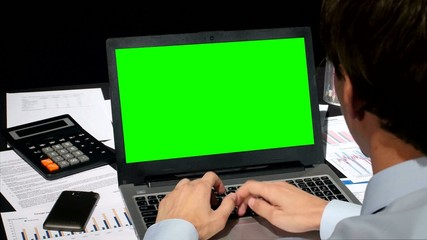 Business people working on his laptop with copy space on a green