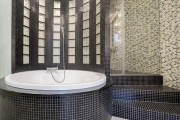 Round bathtub inside black bathroom