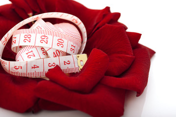 Diet concept. measuring tape isolated in petals of rose flower i